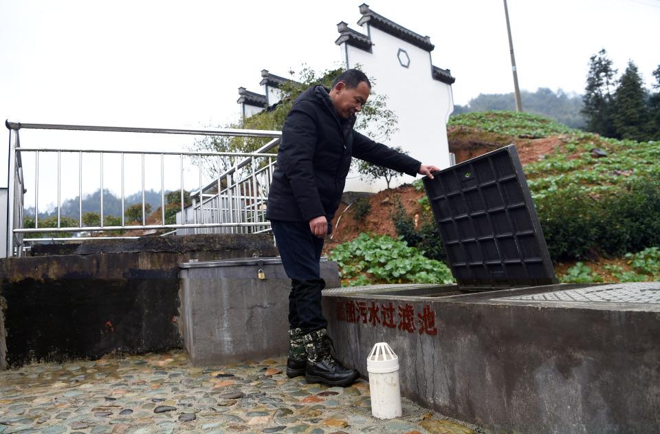 在黄山市歙县的新安江船舶污水上岸收集点,工作人员在查看船舶污水过滤池中的污水过滤情况(据新华社)