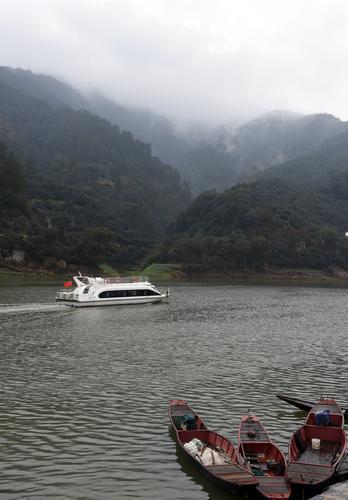 一艘游船行驶在安徽省黄山市歙县的新安江江面上。进行网箱退养之前,河面上网箱遍布,航道很窄。(据新华社)